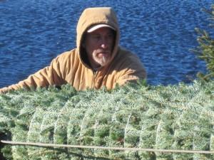 man holding a wrapped Fraser fir